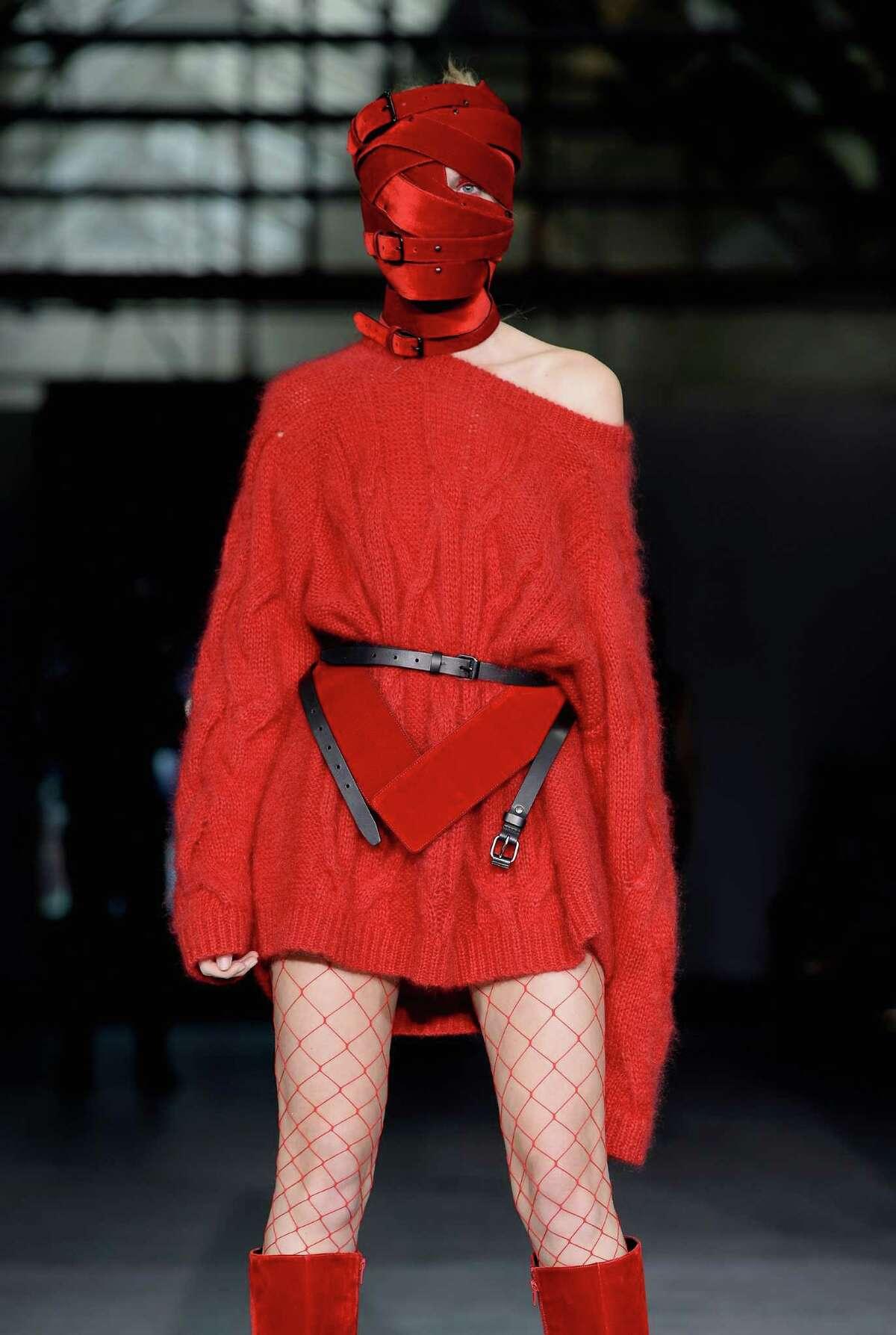Nothing jazzes up fishnet stockings like a terrifying, restrictive face covering made of red velvet belts. (AF Vandevorst)