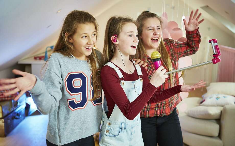 SelfieMic, basically a selfie stick with a microphone on one end, lets kids create and share pop music videos, with the help of an app. Photo: Associated Press