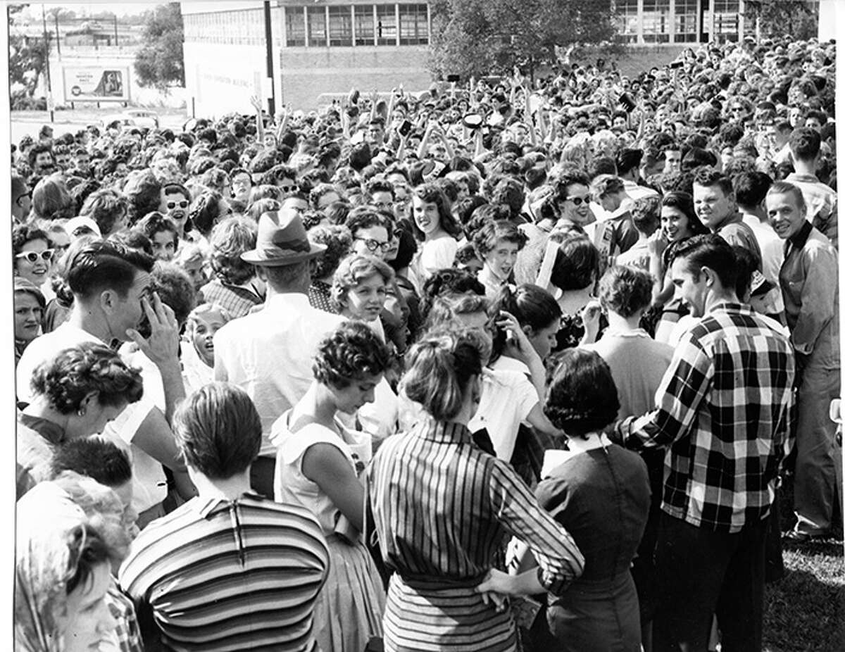 Fans wait in line to see Elvis Presley perform at the Sam Houston Coliseum in Houston. October 13, 1956.
