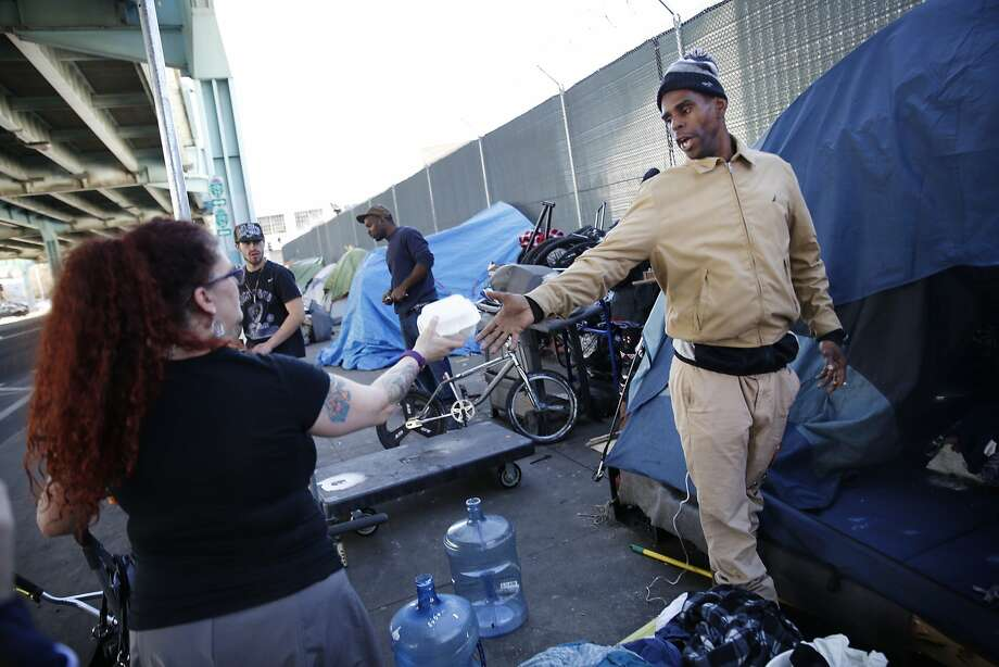 Ashante Jones (right), homeless resident, accepts some fries from Carrie Hamilton, San Francisco resident, as he stands outside his tent on 13th Street on Tuesday,  February 23, 2016 in San Francisco, California. Photo: Lea Suzuki, The Chronicle
