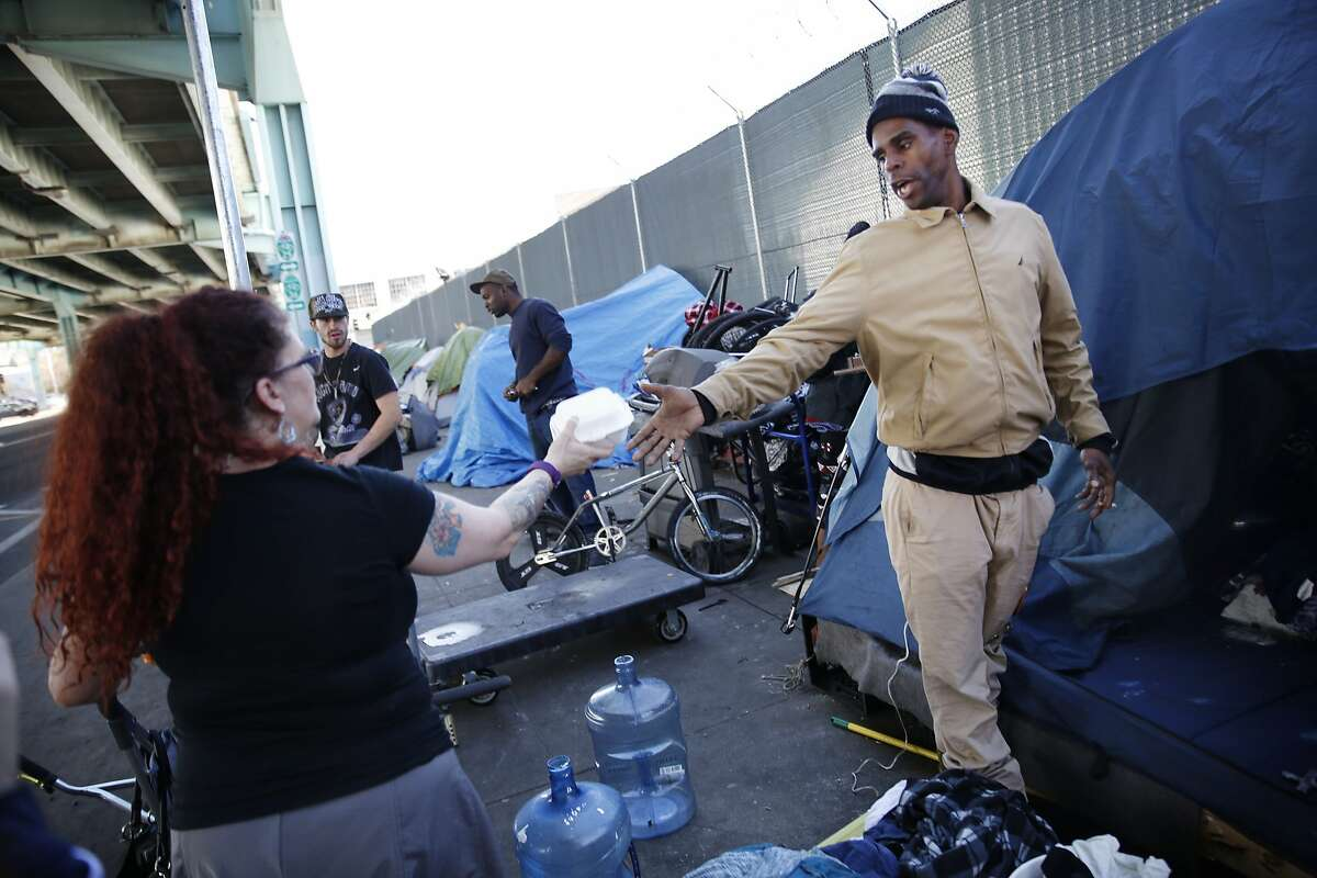 Ashante Jones (right), homeless resident, accepts some fries from Carrie Hamilton, San Francisco resident, as he stands outside his tent on 13th Street on Tuesday, February 23, 2016 in San Francisco, California.