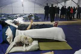 David Tompkins, a homeless client at Pier 80, reads a book while lying on a cot next to his dog Betty as Mayor Ed Lee and others (background right)  tour the shelter at Pier 80 on Tuesday,  February 23, 2016 in San Francisco, California.