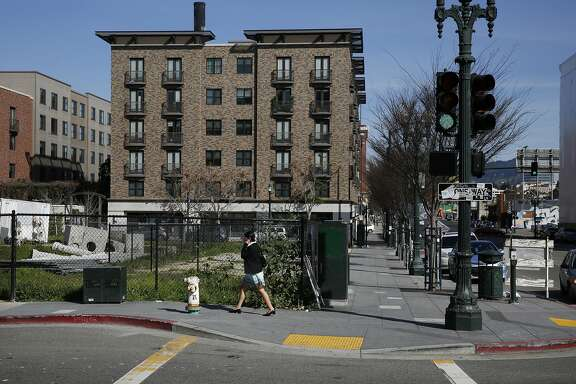 A woman walks past the site of a proposed hotel across from the Fox Theater and the Uptown Apartments Feb. 23, 2016 in Oakland, Calif. the site of a proposed hotel across from the Fox Theater and the Uptown Apartments Feb. 23, 2016 in Oakland, Calif.