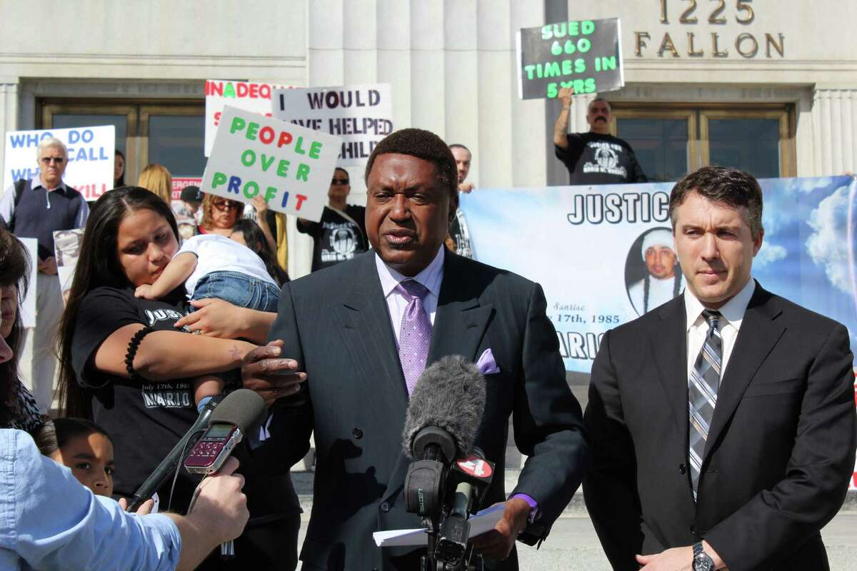 John Burris, center, speaks at a news conference to announce the filing of a federal lawsuit against Alameda County and Corizon Health Inc.