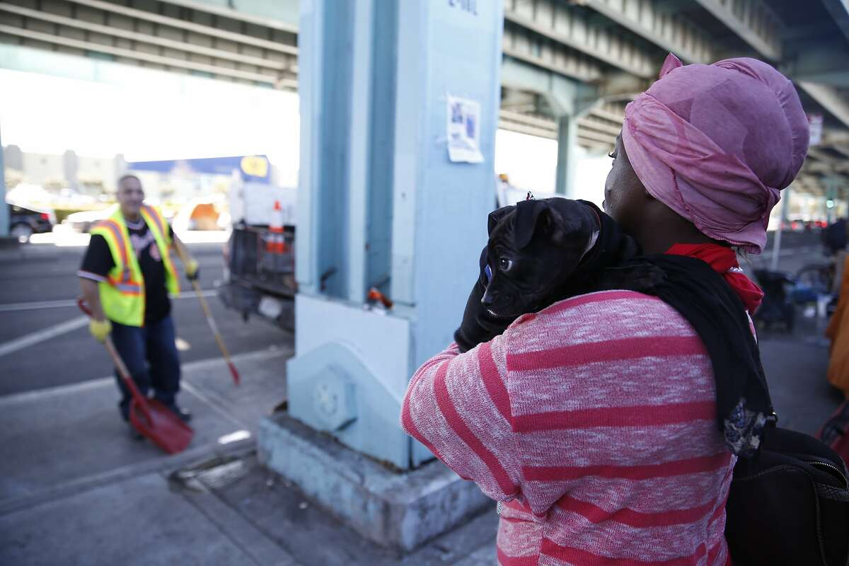 Cassandra Watkins (right), homeless resident, holds her puppy Blackers as she watches Keith Guillory (left), Department of Public Works general laborer, sweet along 13th Street on Tuesday, February 23, 2016 in San Francisco, California.