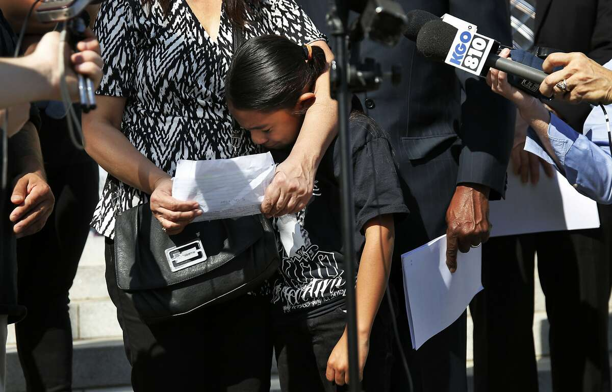 Thalia Martinez, 8, the daughter of the late Mario Martinez cries as her grandmother Tanti Martinez speaks to the press during a rally and press conference outside of the RenŽ C. Davidson Courthouse Feb. 23, 2016 in Oakland, Calif by the family of Mario Martinez who died in Dublin's Santa Rita Jail last year. The family will sue the jail's private health care contractor in federal court for a death they say could have been avoided with proper and more timely treatment.