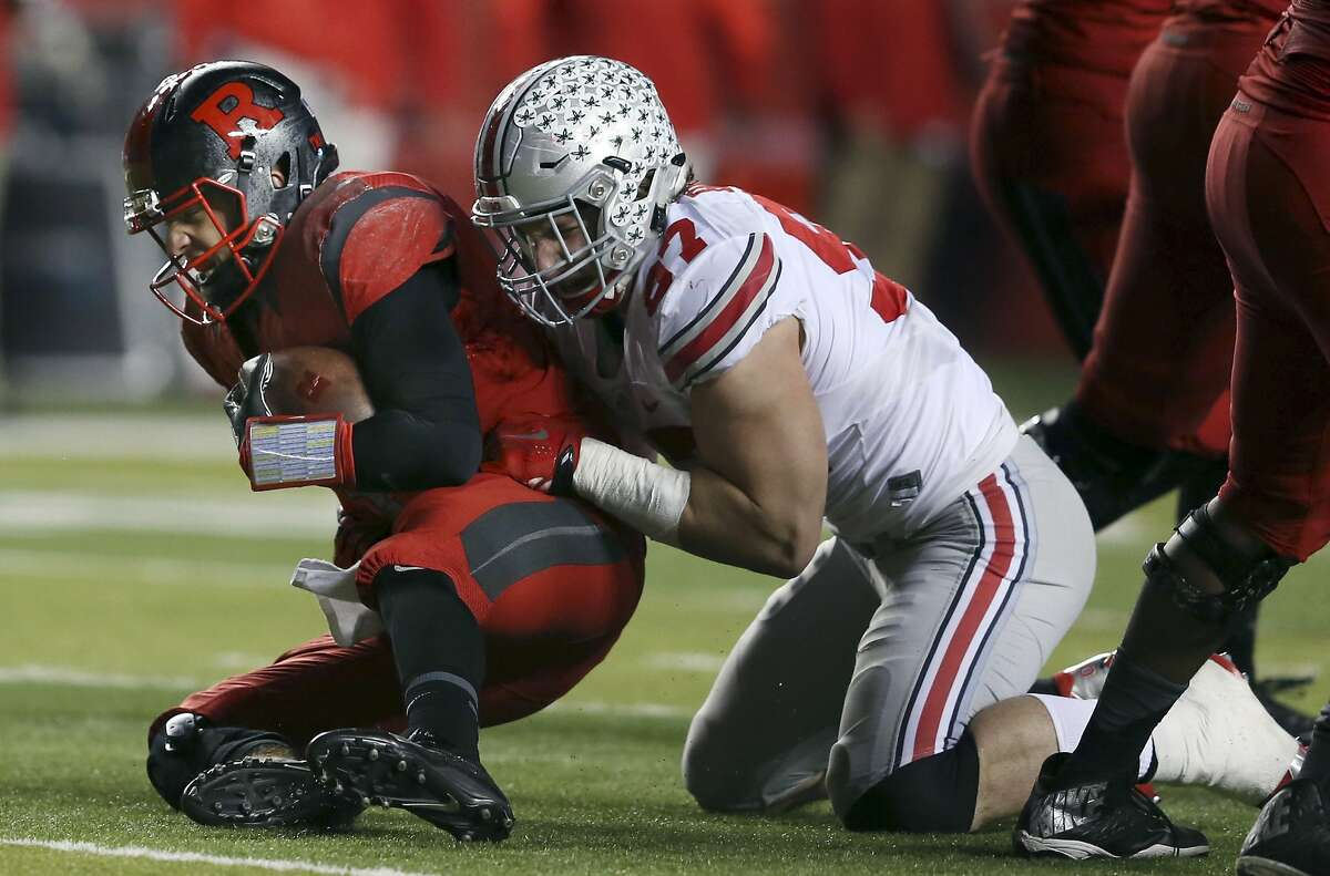 FILE - In this Saturday, Oct. 24, 2015, file photo, Ohio State defensive end Joey Bosa (97) sacks Rutgers quarterback Chris Laviano (5) during the first half of an NCAA college football game in Piscataway, N.J. Either the Tennessee Titans or Cleveland Browns could wind up with No. 1 pick in 2016 NFL Draft. Bosa, with his comparisons to J.J. Watt, would seem to fit into any defensive system, and could be an attractive pick for Cleveland. (AP Photo/Mel Evans, File)