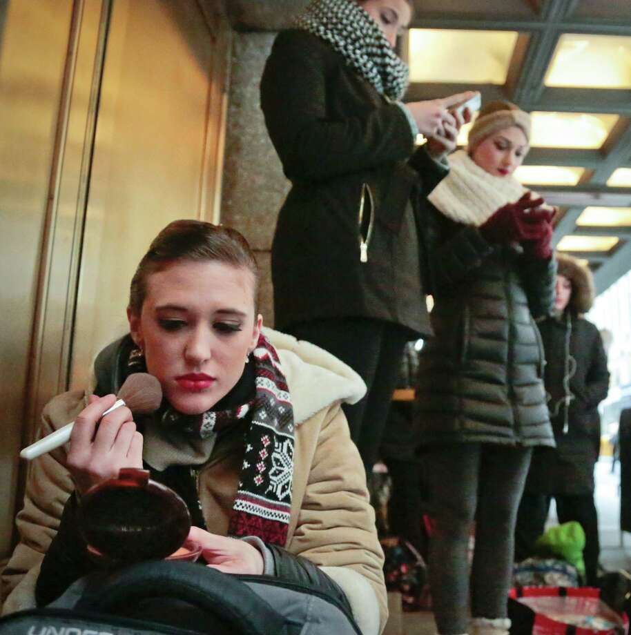 "Courtney Tierchoski, 25, from Nashville, Tenn., applies makeup while on line with other dancers outside Radio City Music Hall waiting to audition for ""Rockettes New York Spectacular"" on Tuesday, Feb. 23, 2016, in New York.  Tierchoski said she hope the third is the charm as she hopes to land a spot in the summertime production from June 15 through Aug. 7, 2016.  (AP Photo/Bebeto Matthews) ORG XMIT: NYBM104 Photo: Bebeto Matthews / AP"