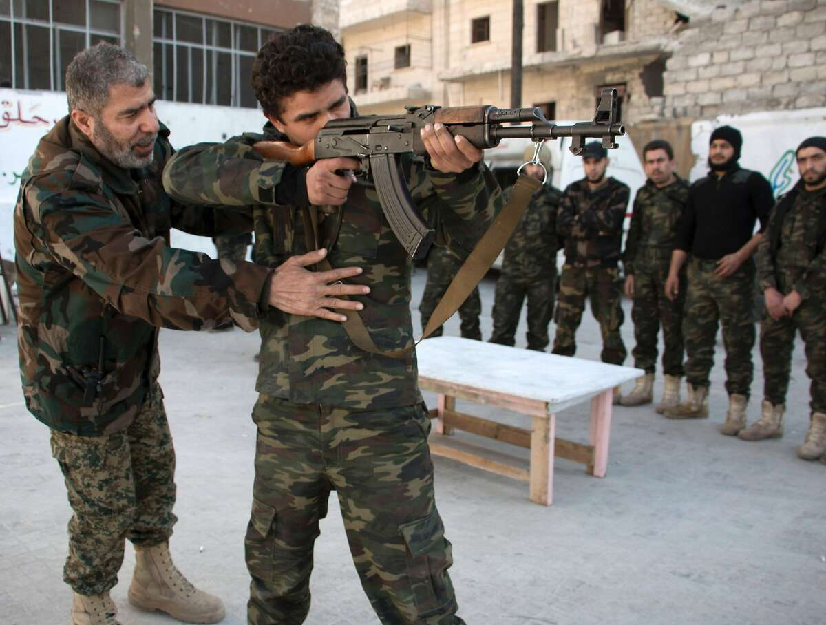 (FILES) This file photo taken on February 16, 2016 shows new recruits taking part in a shooting training session at a camp in a rebel-held area of the northern city of Aleppo before fighting along with opposition fighters. A single road connects the rebel areas of eastern Aleppo to Turkey. The bastion of the Syrian rebellion, being besieged and shelled by aviation, stores weapons and supplies to hold as long as possible.