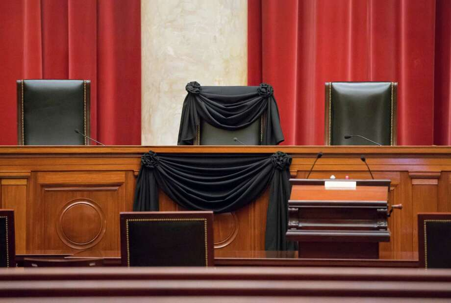 Supreme Court Justice Antonin Scalia's courtroom chair is draped in black to mark his death as part of a tradition that dates to the 19th century, on Tuesday, Feb. 16, 2016, at the Supreme Court in Washington.  (AP Photo/J. Scott Applewhite) Photo: J. Scott Applewhite, STF / AP