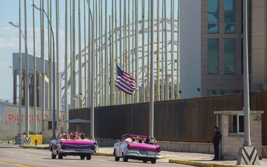 Tourists ride vintage American convertibles as they pass by the United States embassy in Havana, Cuba, Thursday, Feb. 18, 2016. President Barack Obama said that he will visit Cuba on March 21-22, making him the first sitting president in more than half a century to visit the island nation. (AP Photo/Desmond Boylan) Photo: Desmond Boylan, STR / AP