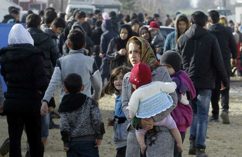 Refugees and migrants, mostly from Afghanistan, walk through the transit center for refugees near the Macedonian village Tabanovce while waiting permission to cross into Serbia on Tuesday. Photo: Boris Grdanoski, STR / AP