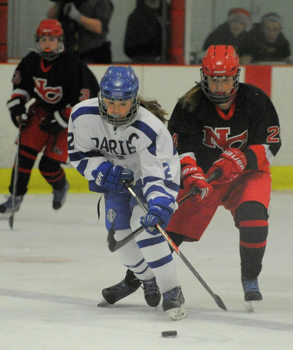 Darien's Georgia Cassidy breaks away from New Canaan's Elizabeth McCarthy during a girls varsity ice hockey game at the Darien Ice Rink in Darien, Conn. on Jan. 16, 2016. Darien won 3-2.