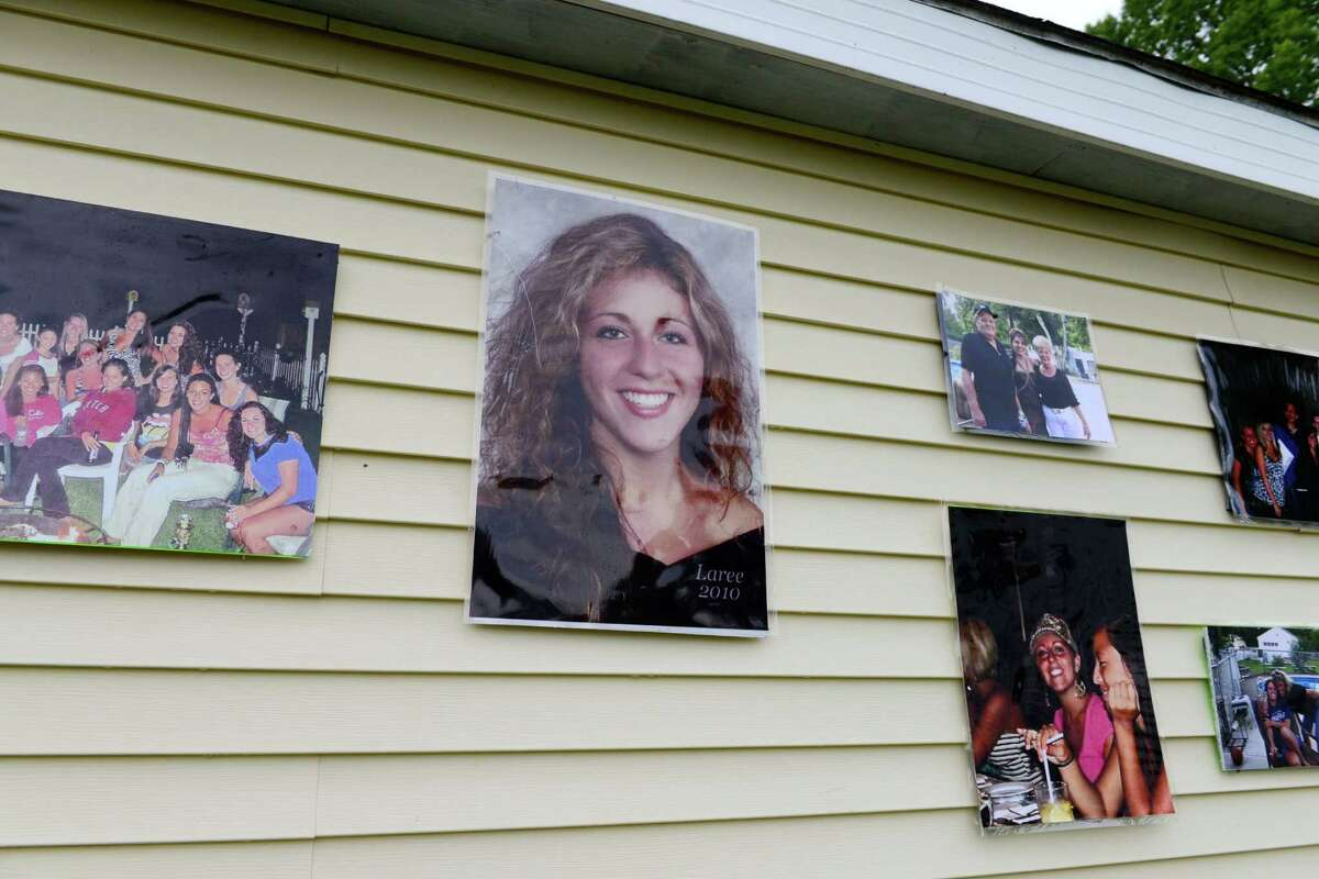 Photos of Laree Farrell hang on a neighbors building next to Patty Farrell's backyard Thursday, May 22, 2014, in Colonie, N.Y. Laree died of a heroin overdose at her mother's home in 2013. (Will Waldron/Times Union archive)