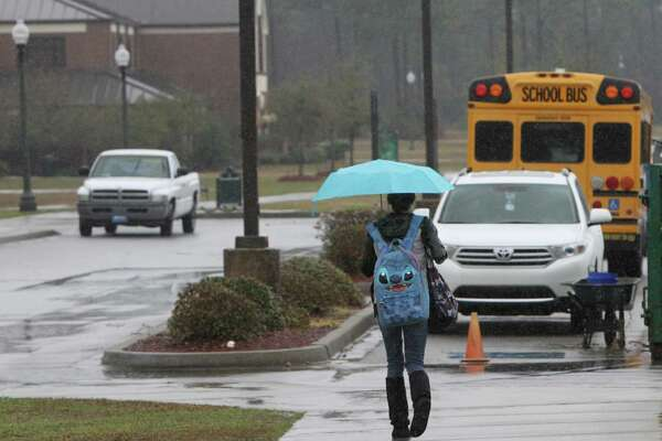 Amanda Hamilton of Biloxi, Miss., walks across campus at Mississippi Gulf Coast Community College Jackson County Campus during a morning rain shower, Tuesday Feb. 23, 2016, in Gautier, Miss. The college system and many other school districts in South Mississippi will close early on Tuesday because of heavy rain expected in the afternoon. (John Fitzhugh/The Sun Herald via AP) LOCAL TELEVISION OUT; MANDATORY CREDIT: MISSISSIPPI PRESS OUT; LOCAL TELEVISION OUT WLOX, LOCAL ONLINE OUT; GULFLIVE.COM OUT