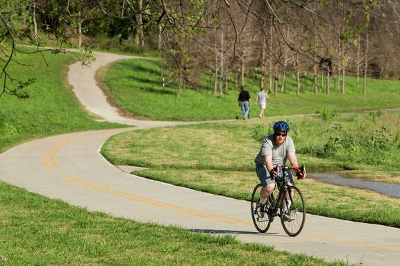 A cyclist uses a trail next to White Oak Bayou. Many of Houston's current bike trails are not connected.