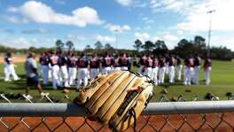 A glove sits atop a fence as players warm up during the first full-squad workouts at the Astros spring training in Kissimmee, Florida, Tuesday, Feb. 23, 2016.( Karen Warren / Houston Chronicle )
