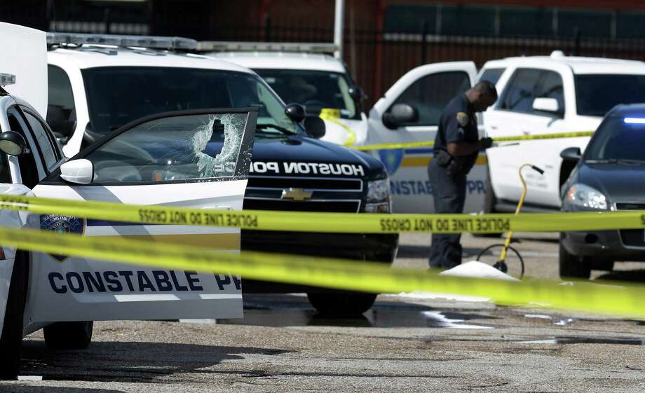 Officers surround the patrol car after a man with a machete smashed the window Tuesday at a bus terminal in the 3200 block of Telephone Road.  ( Melissa Phillip / Houston Chronicle ) Photo: Melissa Phillip, Staff / © 2016 Houston Chronicle