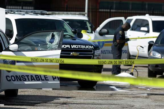 Officers surround the patrol car after a man with a machete smashed the window Tuesday at a bus terminal in the 3200 block of Telephone Road.  ( Melissa Phillip / Houston Chronicle )