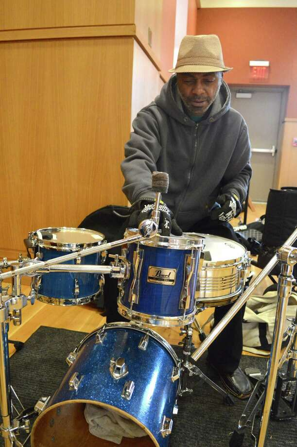 Chuck Batton, drummer for The Silver Fox Songs Trio gets his gear together before Saturday afternoon's show at Darien Library. Photo: Jarret Liotta / Contributed Photo / Darien News