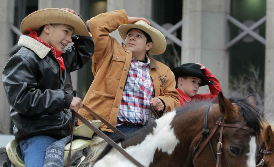 Members of the Texas Independence Trail Ride hold onto their hats as they ride in the Houston Livestock Show and Rodeo Parade in downtown Saturday, Feb. 28, 2015, in Houston. ( Melissa Phillip / Houston Chronicle ) Photo: Melissa Phillip, Staff / © 2014  Houston Chronicle