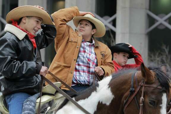 Members of the Texas Independence Trail Ride hold onto their hats as they ride in the Houston Livestock Show and Rodeo Parade in downtown Saturday, Feb. 28, 2015, in Houston. ( Melissa Phillip / Houston Chronicle )