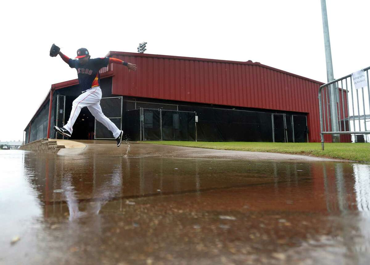 Houston Astros bullpen catcher Carlos Munoz leaps over a large puddle outside of the batting cages, as players worked out inside due to the rain at the Astros spring training in Kissimmee, Florida, Wednesday, Feb. 24, 2016.