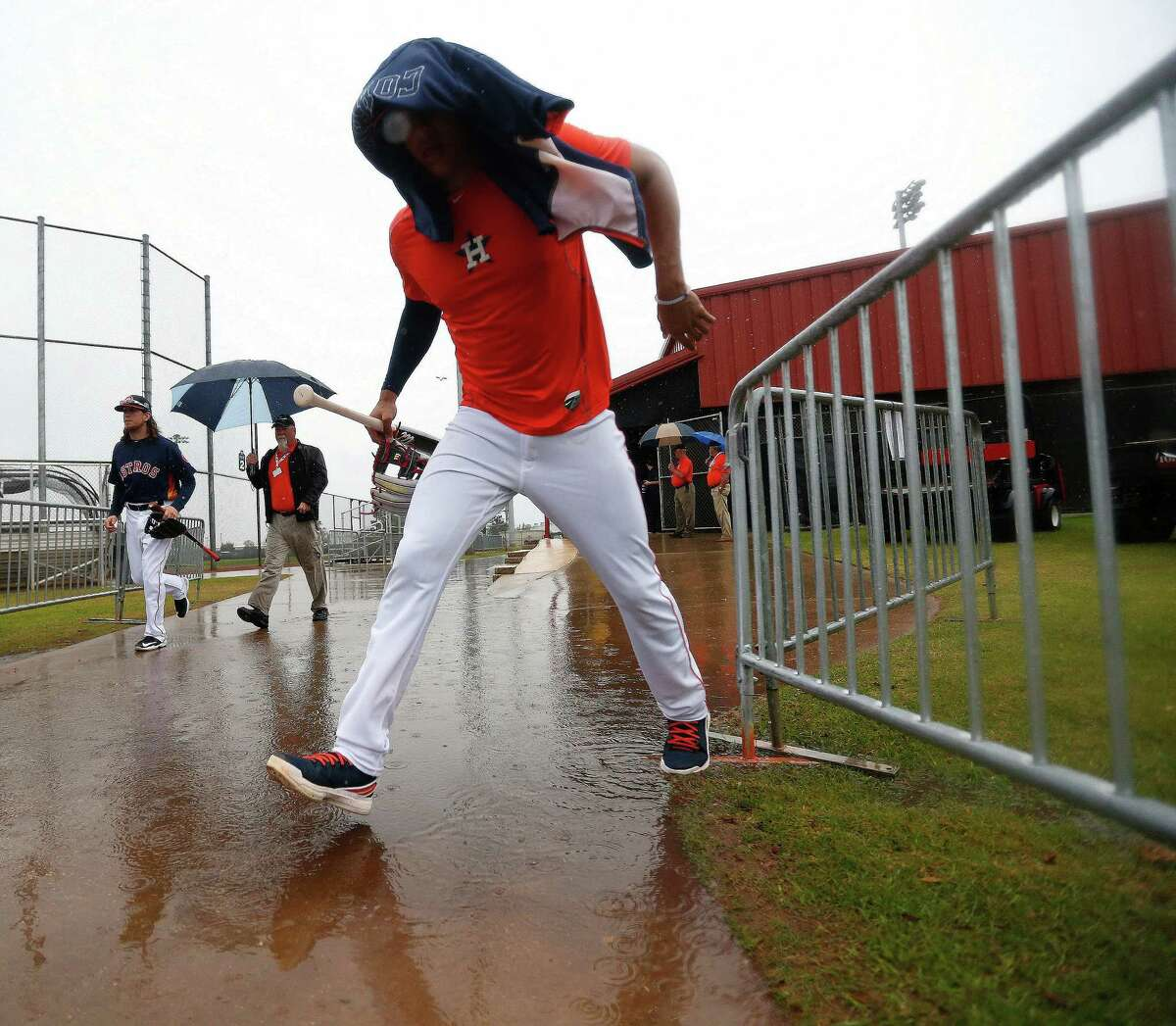 Houston Astros Carlos Correa tries to avoid a puddle, and the rain, as he leaves the batting cages at the Astros spring training in Kissimmee, Florida, Wednesday, Feb. 24, 2016.