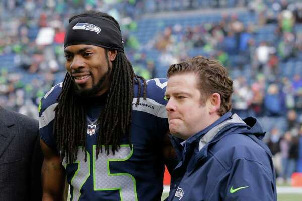 "Seattle Seahawks cornerback Richard Sherman (25) stands with Seahawks general manager John Schneider, right, and president Peter McLoughlin, left, after he was named the Seahawks' ""Man of the Year"" during an NFL football game against the Cleveland Browns, Sunday, Dec. 20, 2015, in Seattle. (AP Photo/Ted S. Warren)"