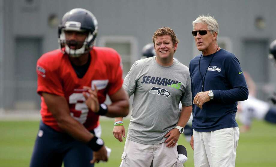 Seattle Seahawks head coach Pete Carroll, right, and general manager John Schneider watch as quarterback Russell Wilson throws at an NFL football training camp Monday, Aug. 3, 2015, in Renton, Wash. Photo: Elaine Thompson, Associated Press / AP