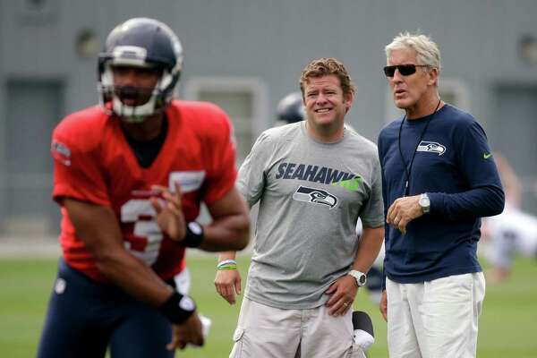 Seattle Seahawks head coach Pete Carroll, right, and general manager John Schneider watch as quarterback Russell Wilson throws at an NFL football training camp Monday, Aug. 3, 2015, in Renton, Wash. (AP Photo/Elaine Thompson)