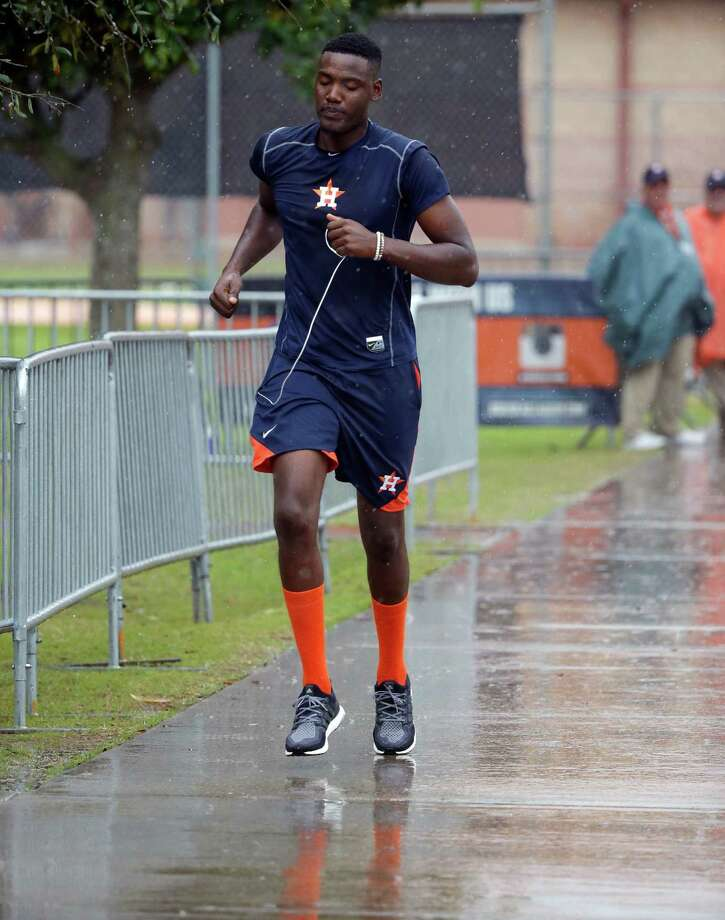 Houston Astros pitcher David Paulino runs through a rain shower to get to an exercise room during a spring training baseball workout, Wednesday, Feb. 24, 2016, in Kissimmee, Fla. (AP Photo/John Raoux) Photo: John Raoux, STF / Copyright 2016 The Associated Press. All rights reserved. This material may not be published, broadcast, rewritten or redistribu