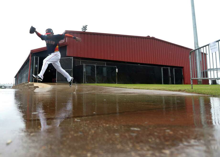 Houston Astros bullpen catcher Carlos Munoz leaps over a large puddle outside of the batting cages, as players worked out inside due to the rain at the Astros spring training in Kissimmee, Florida, Wednesday, Feb. 24, 2016.( Karen Warren / Houston Chronicle ) Photo: Karen Warren, Staff / © 2015  Houston Chronicle