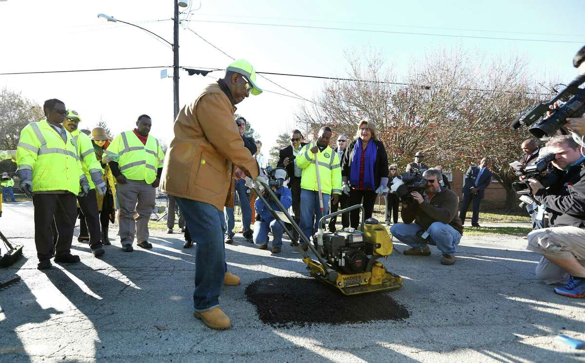 """Mayor Sylvester Turner uses a tapper to fill a pothole at 9733 Neuens Road one day last month. The average rate of successful """"next-business-day"""" pothole repair has been 95 percent since the program began."""