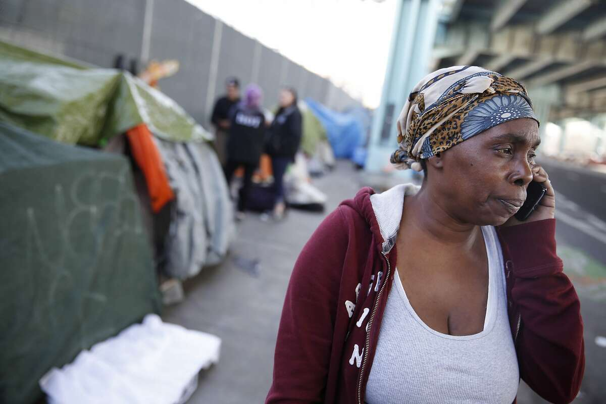 Seanda Conley, of Treasure Island, talks on the phone as she visits with homeless residents along 13th Street on Wednesday, February 24, 2016 in San Francisco, California. Conley has been visiting the area and bringing food, water and clothes to homeless after hearing of their situation.