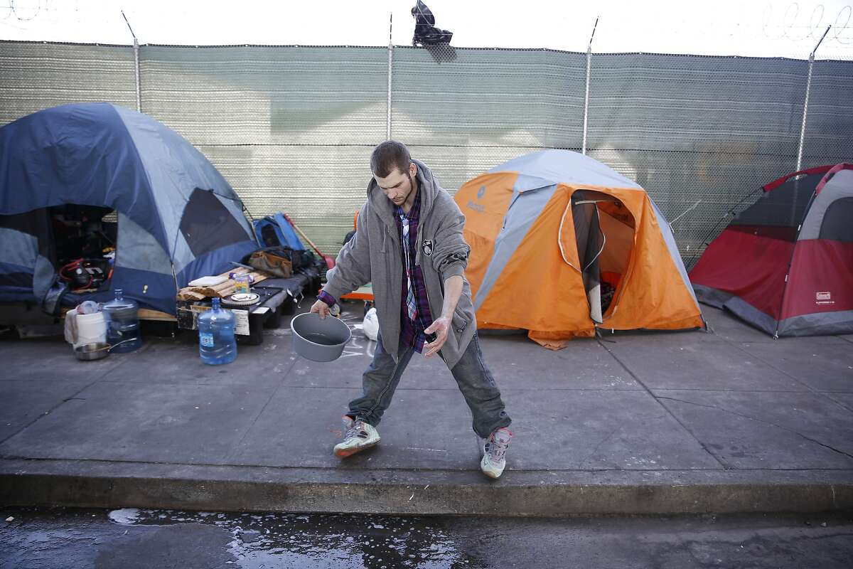 Jeremy Harrell, homeless resident, rinses a wound with water from a bin after washing it to prevent infection along 13th Street on Wednesday, February 24, 2016 in San Francisco, California.