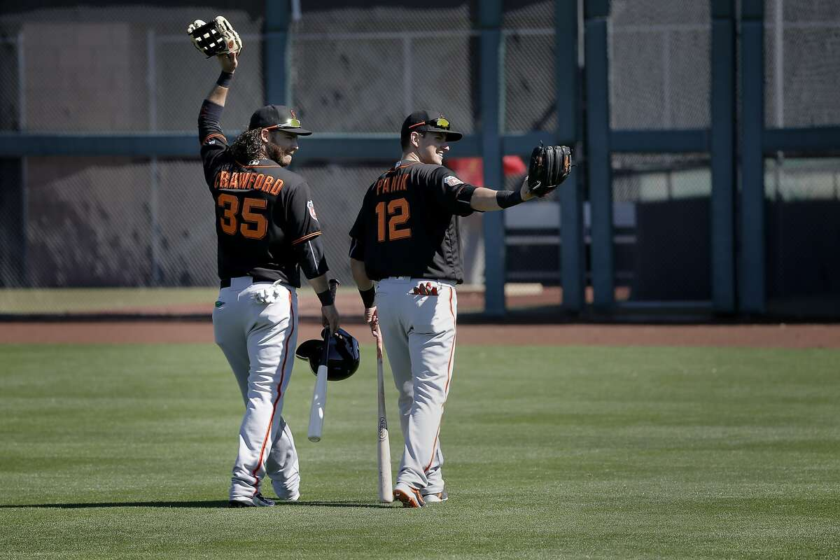 Infielders Brandon Crawford, 35 (left) and Joe Panik, 12 wave to fans in the stands during the San Francisco Giants spring training workouts at Scottsdale Stadium on Wed. February 24, 2016, in Scottsdale, Arizona