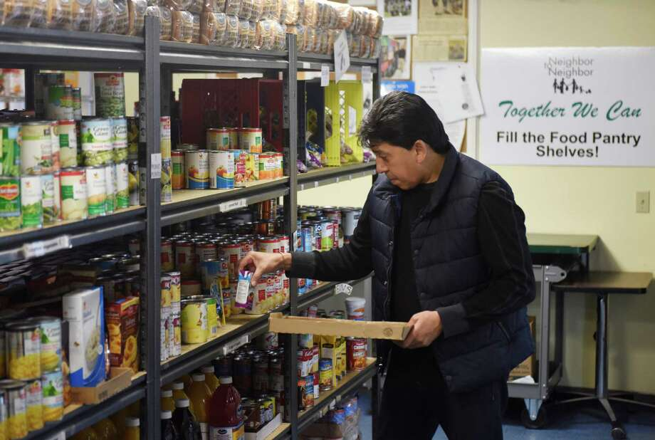 Volunteer Ramon Andrade organizes canned goods on the shelf at the food pantry at Neighbor to Neighbor. The organization is seeking to expand and update its facility. Photo: Tyler Sizemore / Hearst Connecticut Media / Greenwich Time