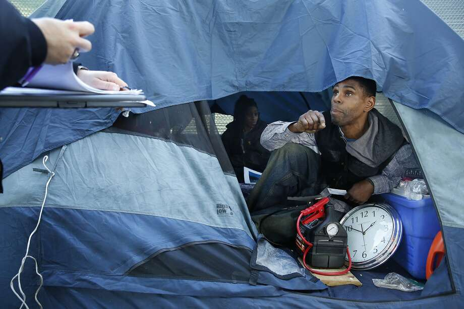 Ashante Jones (right) homeless resident, talks with a Homeless Outreach Team worker (left) while sitting in his tent along 13th Street on Wednesday,  February 24, 2016 in San Francisco, California Photo: Lea Suzuki, The Chronicle