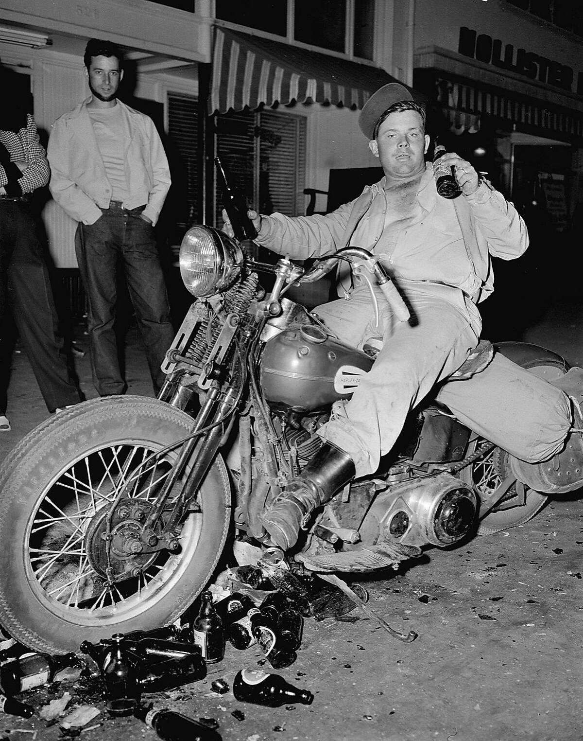MOTORCYCLES IN HOLLISTER - EDDIE DAVENPORT, OF TULARE, CA, DRINKS A BEER ON HIS MOTORCYCLE IN HOLLISTER, CA. DURING THE DISRUPTION OF JULY 7, 1947. August Deserpa, left, watches from the background. Photo by Barney Peterson, SF Chronicle Over the years, confusion of the name of the biker has been reported as Eddie Davenport or Don Middleton.