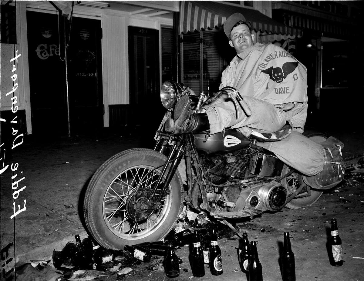 """HOLLISTER9/B/07JUL47/MN/BP - EDDIE DAVENPORT, OF TULARE, CA, DRINKS A BEER ON HIS MOTORCYCLE IN HOLLISTER, CA. DURING THE DISRUPTION OF JULY 7, 1947. The attitude of the motorcyclists was expressed by one youth today in the words: """"Well, the American Legion goes into a town and raises hell. It's a convention. We're just hvaing a convention..."""" Photo by Barney Peterson Over the years, confusion of the name of the biker has been reported as Eddie Davenport or Don Middleton."""