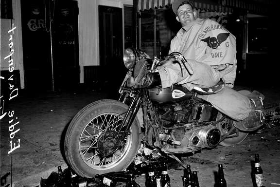 "HOLLISTER9/B/07JUL47/MN/BP - EDDIE DAVENPORT, OF TULARE, CA, DRINKS A BEER ON HIS MOTORCYCLE IN HOLLISTER, CA. DURING THE DISRUPTION OF JULY 7, 1947.  The attitude of the motorcyclists was expressed by one youth today in the words:  ""Well, the American Legion goes into a town and raises hell.  It's a convention.  We're just hvaing a convention...""  Photo by Barney Peterson   Over the years, confusion of the name of the biker has been reported as Eddie Davenport or Don Middleton."