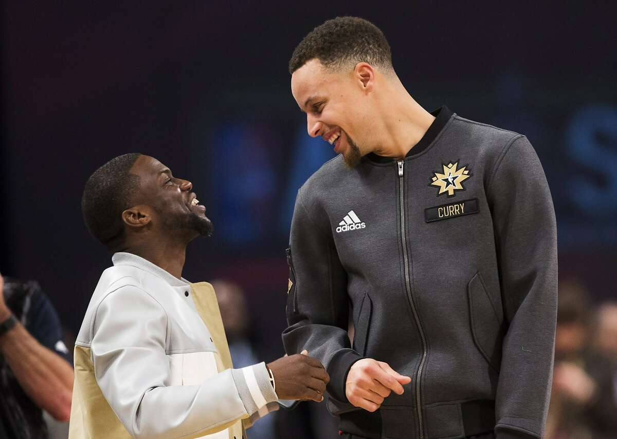 Actor Kevin Hart talks with Golden State Warriors guard Stephen Curry (30) before the first half of the NBA all-star basketball game, Sunday, Feb. 14, 2016 in Toronto. (Mark Blinch/The Canadian Press via AP) MANDATORY CREDIT