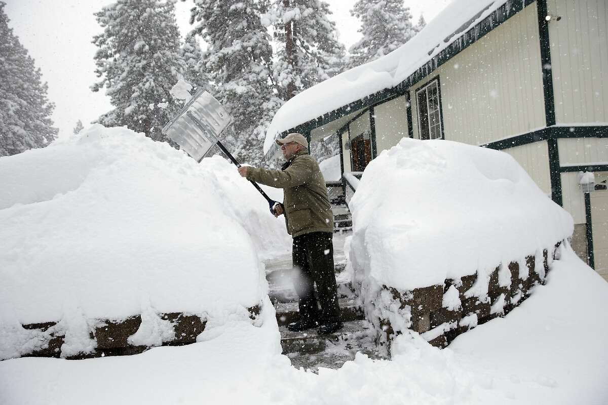 Harry Henneman clears snow from the front steps of his daughter's house Thursday, Feb. 18, 2016, in Truckee, Calif. A storm packing rain and high winds downed power lines, toppled trees and delayed flights across California, bringing back winter weather after several days of record-heat. In the Sierra Nevada, the winter storm dropped 1 to 2 feet of light powdery snow late Wednesday, adding to a snowpack that could ease but not end drought conditions when it melts in the spring. (AP Photo/Marcio Jose Sanchez)