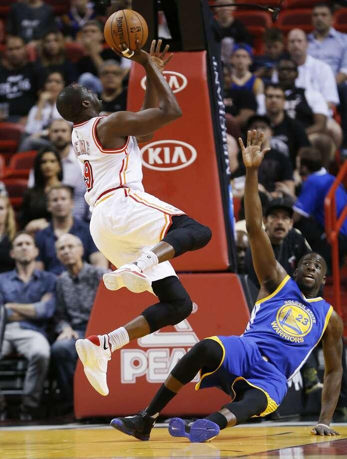 Heat forward Luol Deng (9) shoots as Warriors forward Draymond Green falls during the first half Wednesday at Miami. Photo: Wilfredo Lee, Associated Press