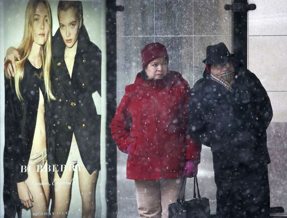 A couple waits for a bus on Chicago's Magnificent Mile as a winter storm begins with blowing snow and high winds off Lake Michigan in the greater Chicago and northwest Indiana area Wednesday, Feb. 24, 2016, in Chicago. The storm is moving through parts of the Midwest stretching from Missouri northeast through Illinois, Indiana and Michigan, with blizzard warnings for counties in eastern Illinois and northwestern Indiana. (AP Photo/Charles Rex Arbogast) ORG XMIT: ILCA101 Photo: Charles Rex Arbogast / AP