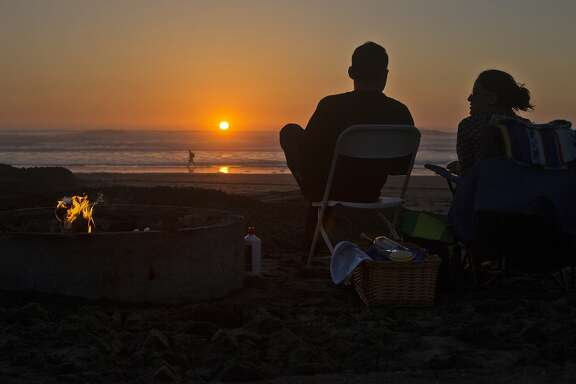 Jacob Larin of San Francisco, and Elise Harb, of Oakland, watch the sun set next to their fire pit on Ocean Beach on Wednesday, February 24, 2016 in San Francisco, Calif.