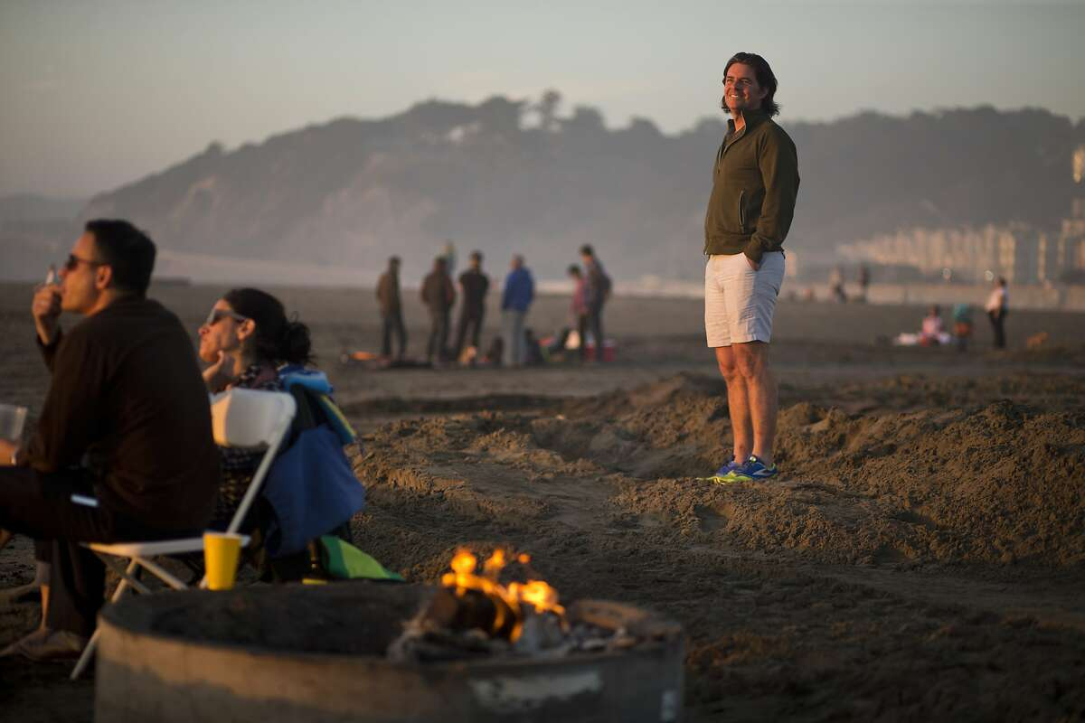 Tom Price, of Burners without Borders, poses among fire rings on Ocean Beach on Wednesday, February 24, 2016 in San Francisco, Calif. Price helped the effort to prevent the National Park Service from imposing more limitations on bonfires at Ocean Beach including requiring permits.