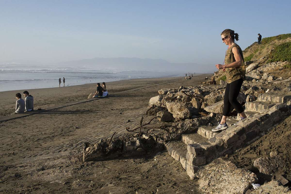 Beach-goers walk down the unearthed cobble-stone stairs and seawall near Taraval Street on Ocean Beach on Wednesday, February 24, 2016 in San Francisco, Calif.