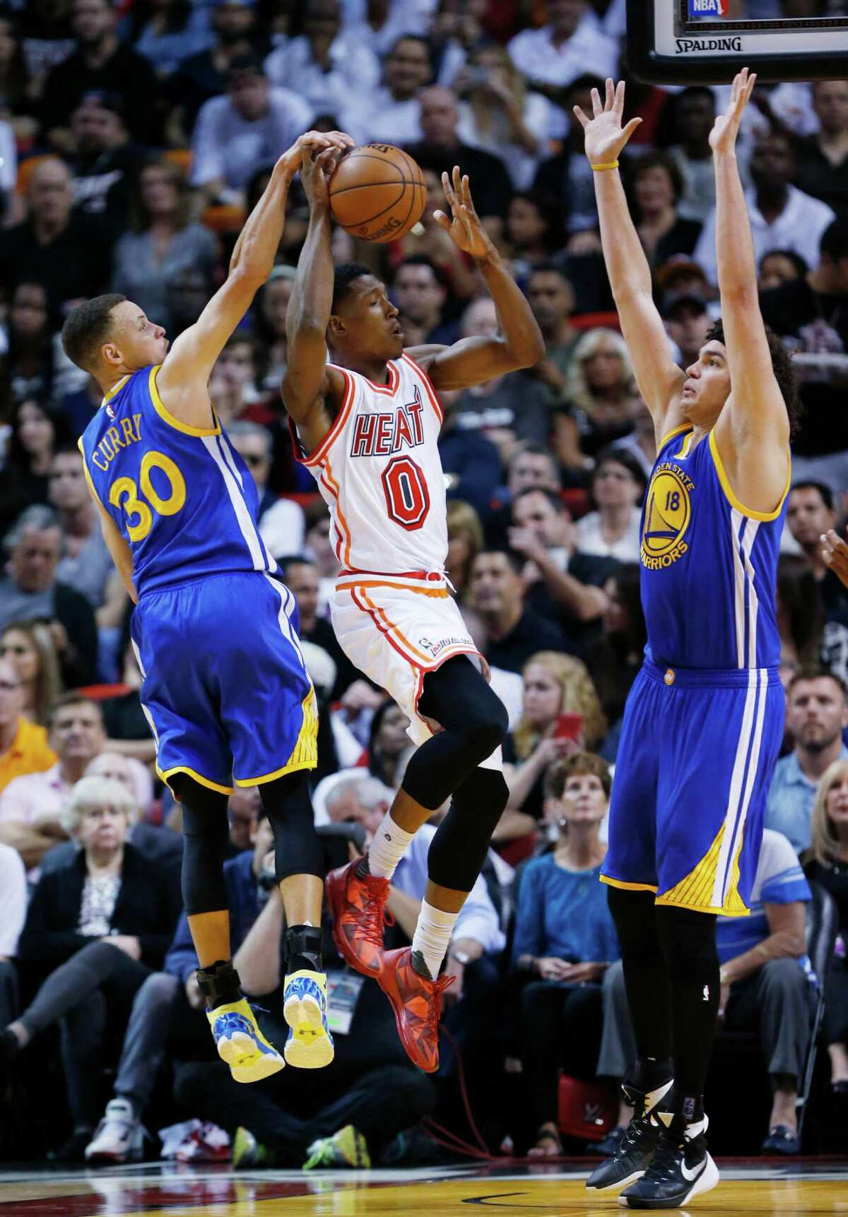 Miami Heat guard Josh Richardson (0) goes up for a shot against Golden State Warriors guard Stephen Curry (30) and center Anderson Varejao (18) during the first half of an NBA basketball game Wednesday, Feb. 24, 2016, in Miami.